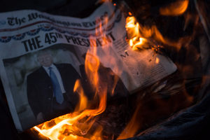 A few violent members of the anti-Trump protest at Franklin Square light trashcan fires in the middle of the street using Trump paraphernalia and todays Inaugural newspaper edition for fuel.