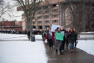 Arva Hassonjee (green sign) and Nedda Sarshar (megaphone) lead hundreds of students down Syracuse University's promenade on Thursday, Feb. 2, 2017 in a