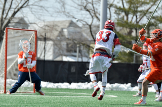 St. John's Joe Madsen fires off a shot toward SU goalie Evan Molloy.