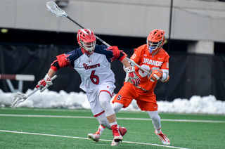 Long stick midfielder Austin Fusco works on St. John's Corey Haynes.